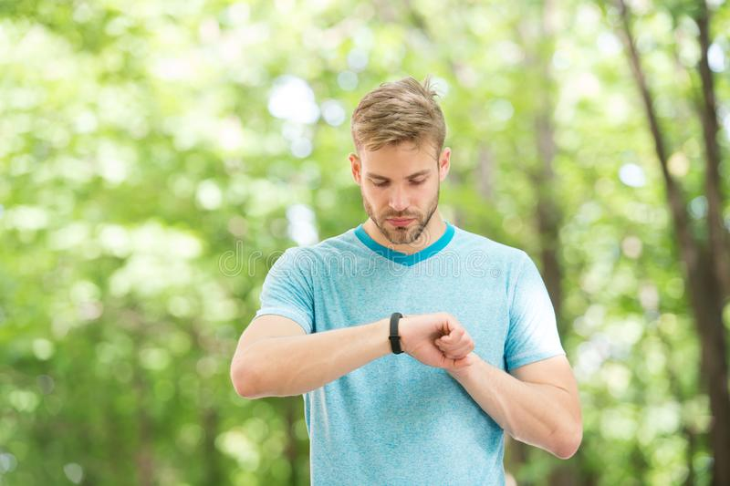 Wearable technologie Knappe atleet die smartwatch technologie gebruiken tijdens opleiding openlucht Geschikte atleet die van hem  royalty-vrije stock afbeeldingen