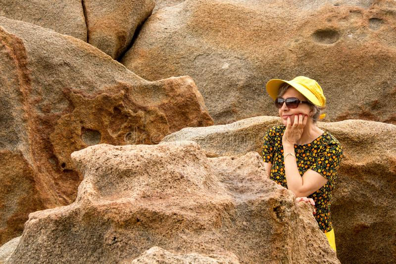 Wearing夫人在海滩的黄色成套装备 免版税库存图片