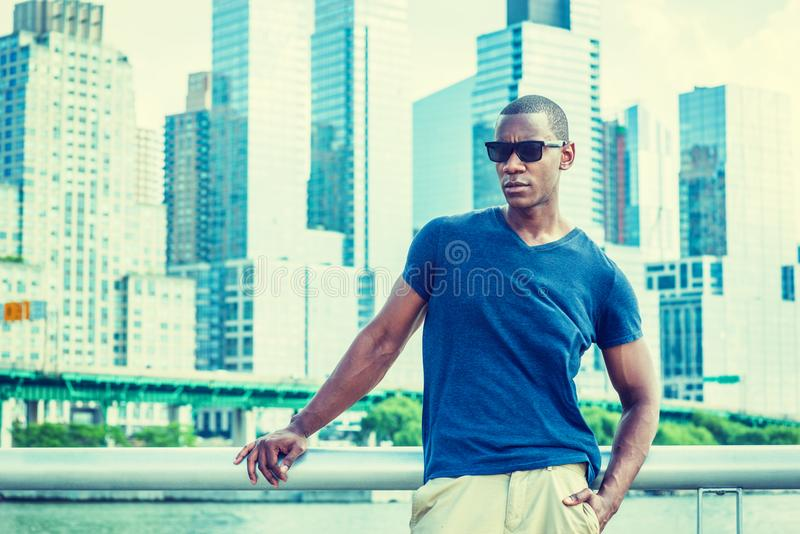 African American Man traveling in New York. Wearing blue V neck T shirt, sunglasses, a black professional standing in business district with high buildings royalty free stock photography