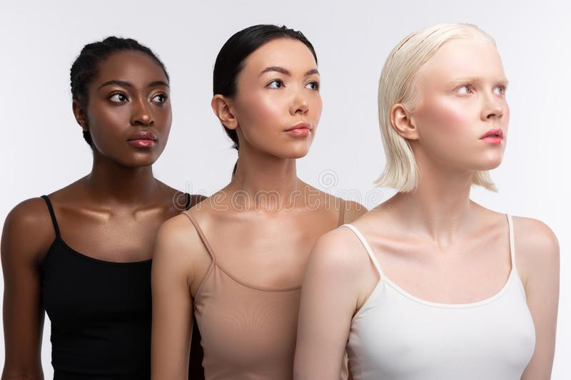 Three women with different skin color wearing camisoles royalty free stock photography