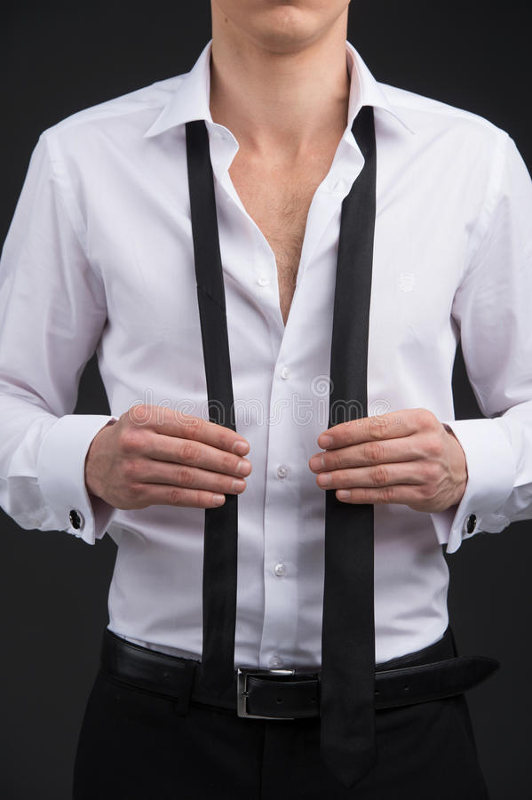 Wearing classical suite. Close up of man starting tying a tie royalty free stock images