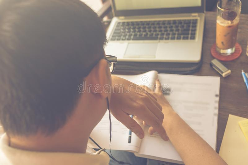 Wearing glasses Asian student studying with laptop and workbook stock photography