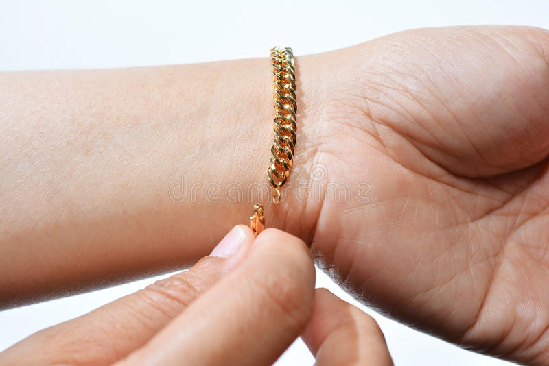 Wearing Gold Bracelet. Woman's Wearing Gold Bracelet on the left hand royalty free stock photos