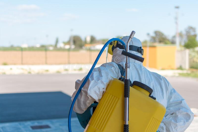 Wearing an NBC personal protective equipment ppe suit, gloves, mask, face shield, cleaning the streets with a backpack of. Pressurized spray disinfectant water stock images