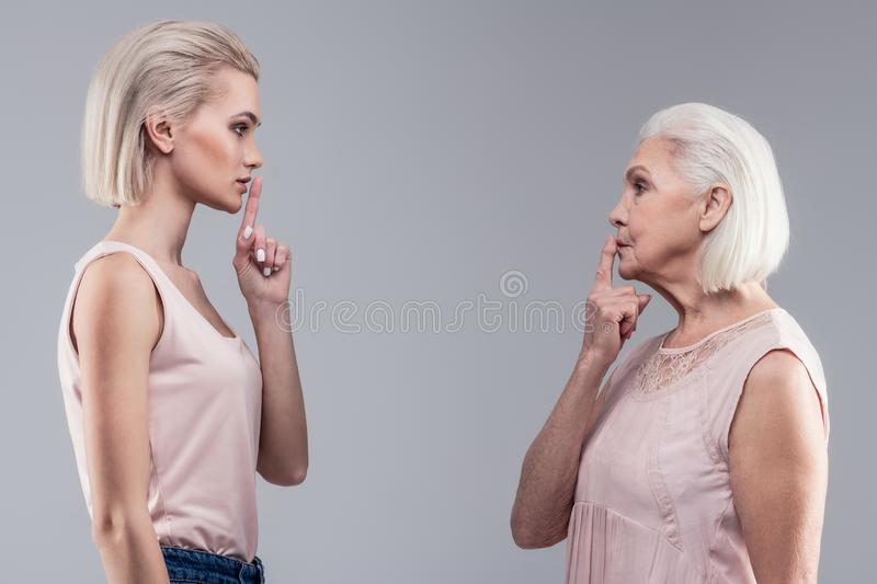 Serious short-haired ladies holding their fingers close to mouths stock images