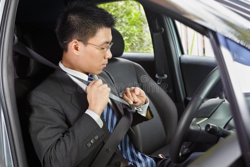 Wearing seat belt. Chinese businessman inside car wearing seat belt royalty free stock photos