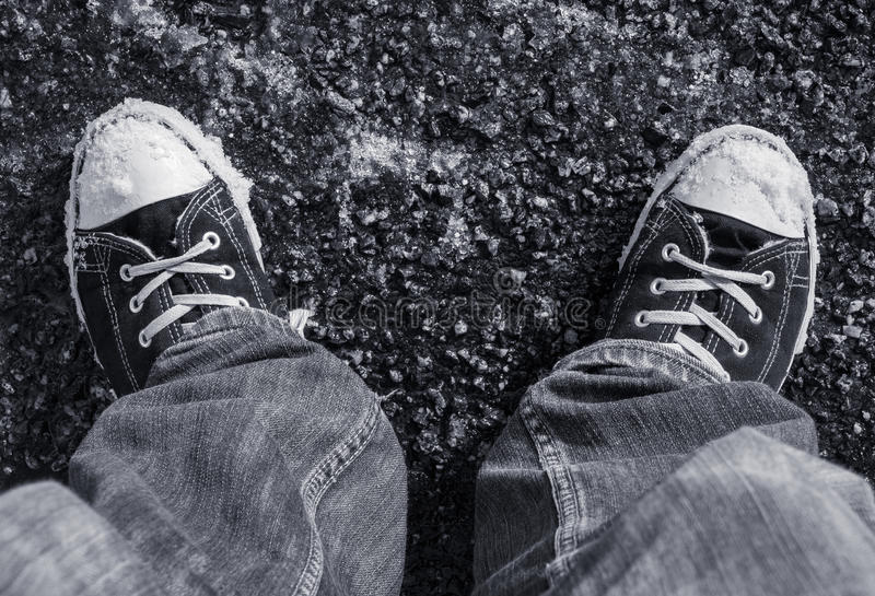 Wearing sneakers in Winter. Legs and feet of person wearing laced sneakers standing on a tarmac surface with flakes of snow beginning to cover the ground stock photography