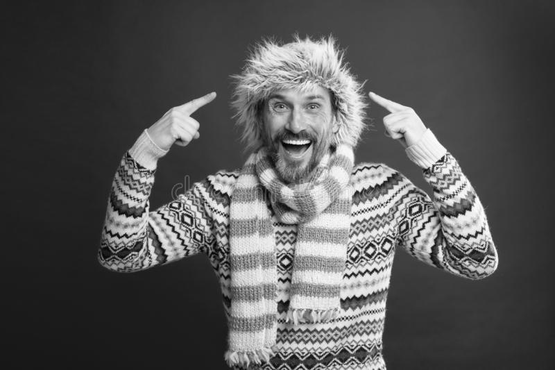 Wearing some key winter accessories. Bearded man in sweater and scarf pointing at hat. A winter ensemble protects him royalty free stock photography
