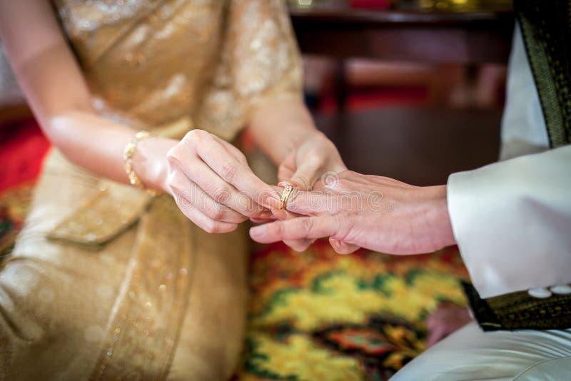 Wearing wedding ring. Thai bride wearing wedding ring for her groom royalty free stock photo