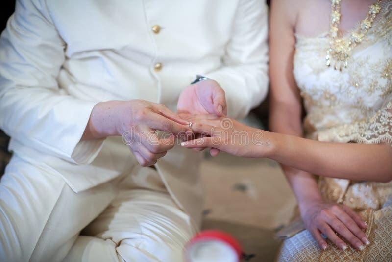 Wearing wedding ring. Thai groom wearing wedding ring for his bride stock photos