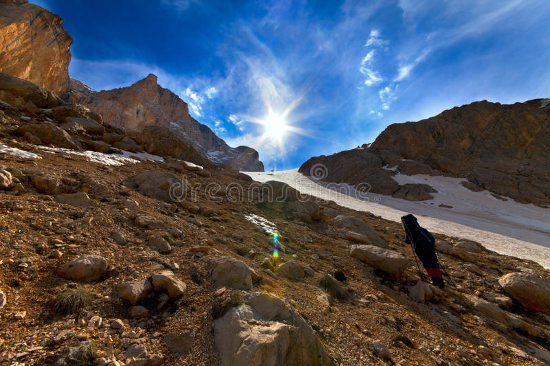 Weary hiker ascent to mountain pass in evening royalty free stock image