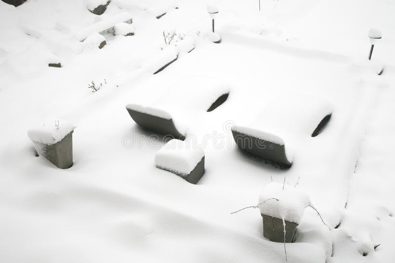 Weather anomaly. Snow in May. Garden covered with snow after snowstorm. Europe. Gloomy day royalty free stock image