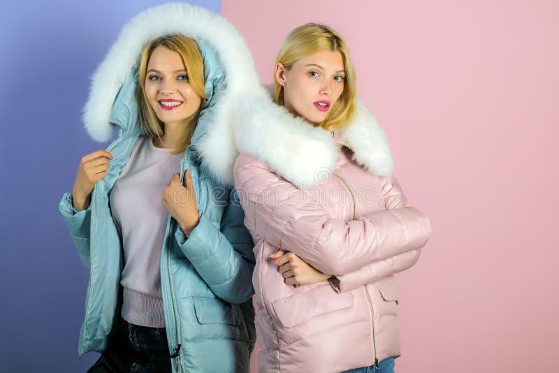 For a weather appropriate winter look. Pretty women in fashionable puffers. women wear warm winter coats. Fashion. Models in hoods with fur. Winter fashion royalty free stock image