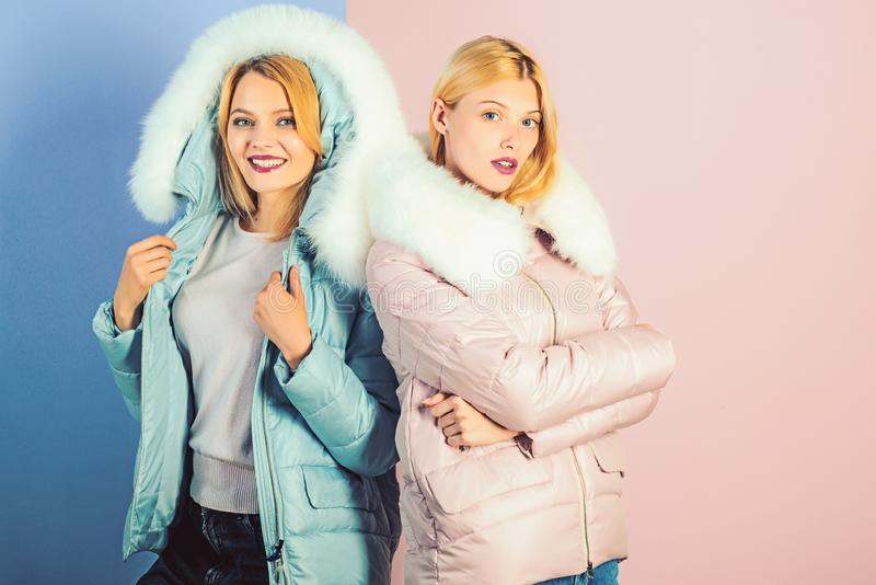 For a weather appropriate winter look. Pretty women in fashionable puffers. women wear warm winter coats. Fashion. Models in hoods with fur. Winter fashion stock images
