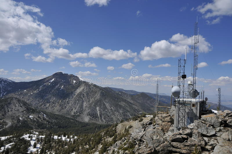 Weather and Communication Site. Weather and Telecommunication Station on Top of Mountain Peak with Clouds and Towers in Background royalty free stock photo