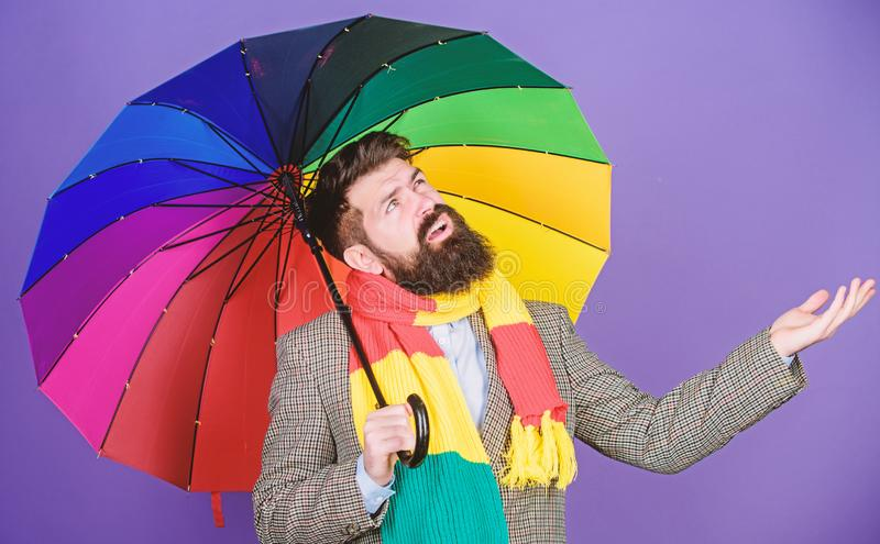 Weather forecast concept. Man bearded hipster hold colorful umbrella. It seems to be raining. Rainy days can be tough to. Get through. Prepared for rainy day royalty free stock photography