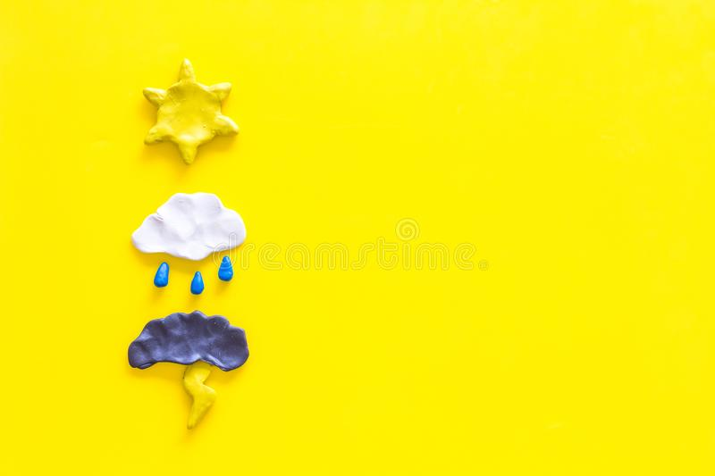 Weather forecast concept. Modern weather icons set on yellow background top view copy space. Weather forecast concept. Modern weather icons set on yellow royalty free stock photo