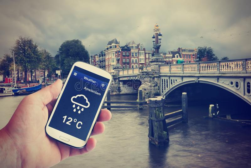 Weather forecast. It`s raining. Canal old bridge cloudy cityscape. Amsterdam, Netherlands royalty free stock image
