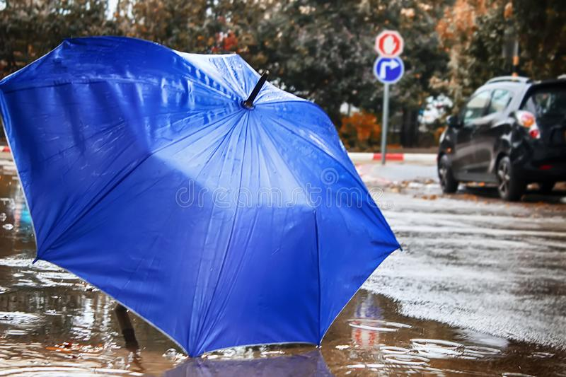 Winter Weather in Israel. Rain, umbrella in the formed puddle, circles on the water and raindrops. Weather in Israel, Winter. Rain, umbrella in the formed puddle stock image