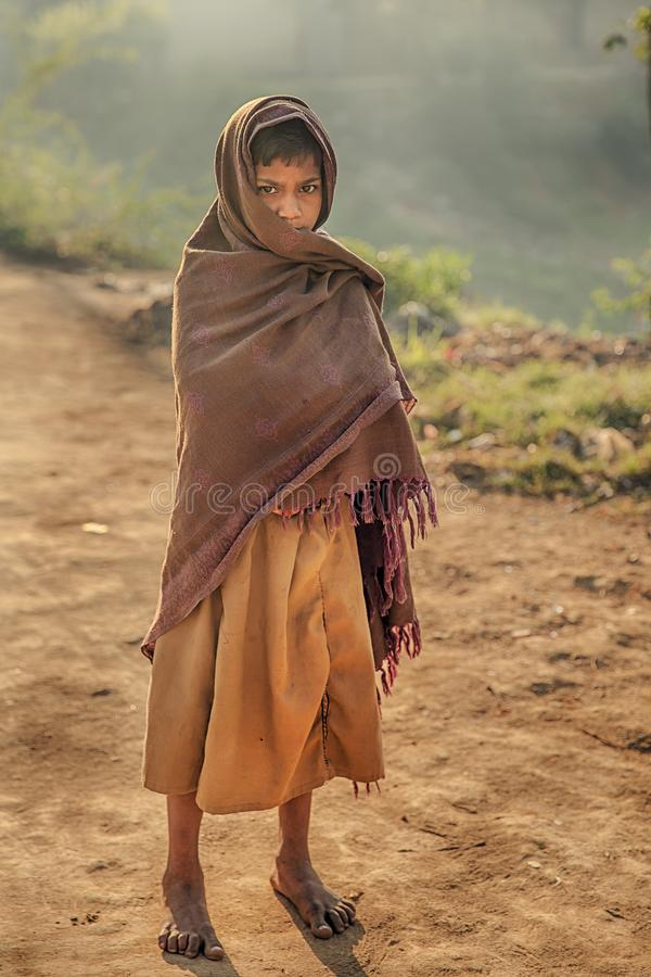 A teenager in the cold wind. The weather is still cold in the early March in India. A rural Indian teenager wrapped in a blanket was walking slowly towards me royalty free stock image