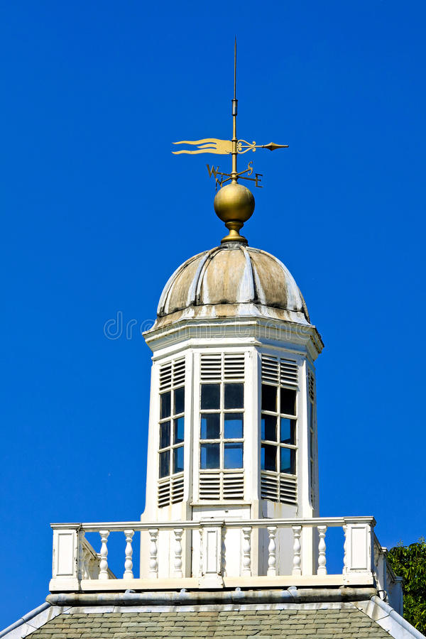 Weather vane. Weather wind vane at white wooden rooftop stock images