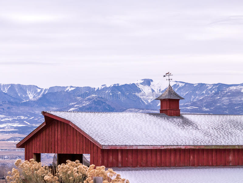 Weather Vane on Red Barn, Winter. Red sided barn with weather vane in front of snowy mountains royalty free stock image
