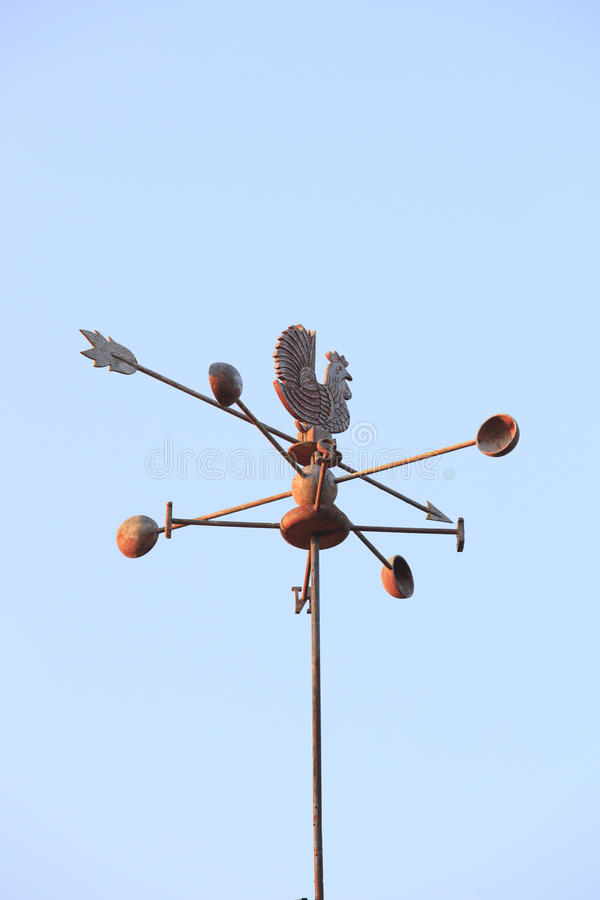 Weather Vane compass over house roof against blue sky background royalty free stock image