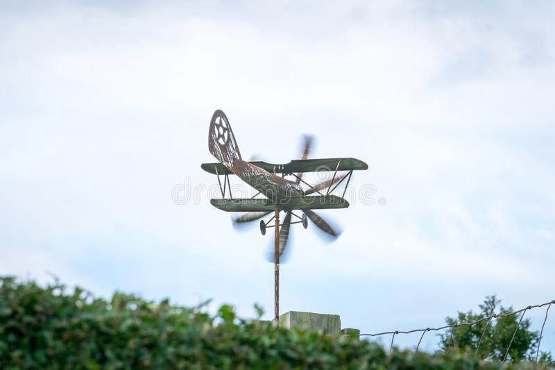 Weather vane in form of an old rusty biplane at a back angle, with propellers moving royalty free stock photography