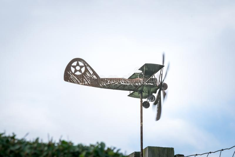 Weather vane in form of an old rusty biplane, at a side-view close-up, with propellers moving stock images