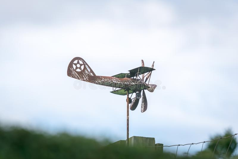 Weather vane in form of an old rusty biplane, at a side-view, with propellers not moving royalty free stock images