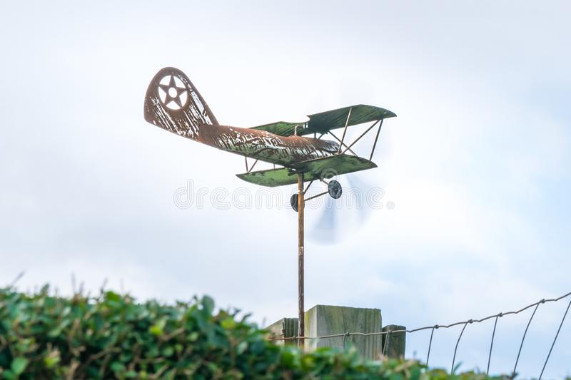 Weather vane in form of an old rusty biplane, at a 3/4 view close-up, with propellers moving fast royalty free stock photography