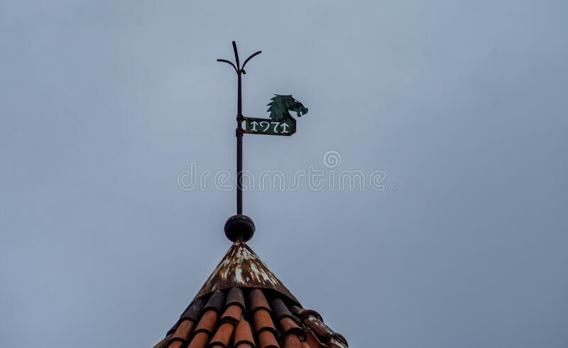 Weather vane on the roof. Weather vane with the inscription 1971 on the tiled roof of an old house in Tallinn stock image