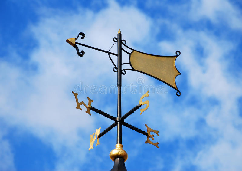 Weather vane in London street. Weather vane on blue sky with clouds in London street royalty free stock photography