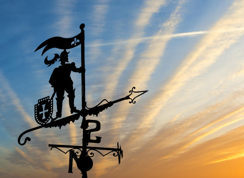Weather vane at sunset. Weather vane is instrument showing direction of wind - typically used as an architectural ornament to the highest point of a building stock image