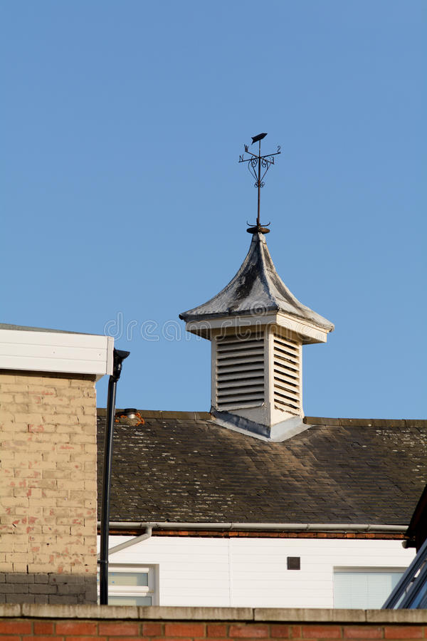 Weather vane on top of building. Weather vane on tower on building roof stock photo
