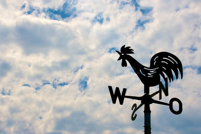 Weathercock on cloudy sky