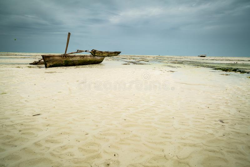 Weathered wooden fishing boat on white sand beach in Zanzibar. Photograph of worn wooden fishing boat resting on the white sand beach in Zanzibar; cloudy skies royalty free stock image