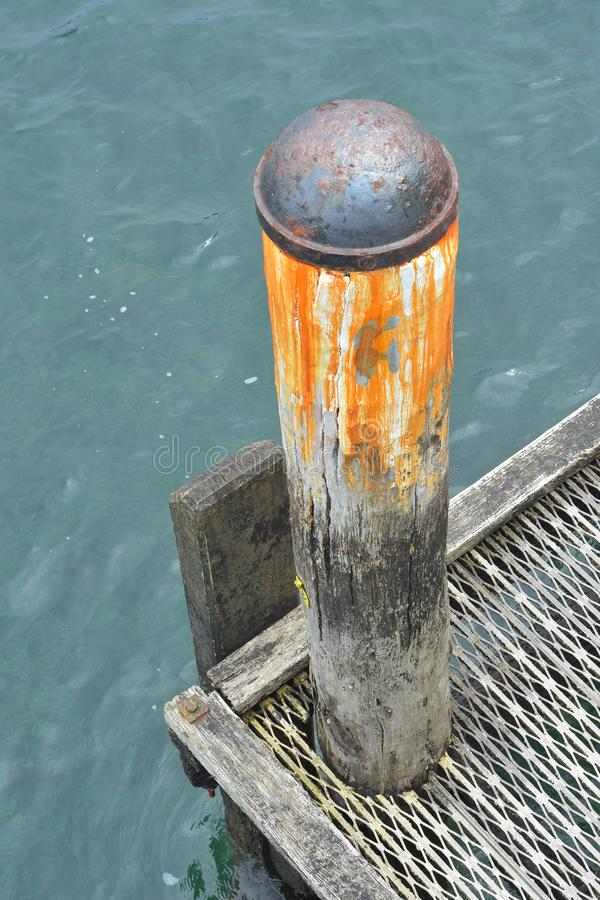 Weathered wooden jetty pole. Weathered big bore wooden jetty pole with rusty iron cap on top royalty free stock photos