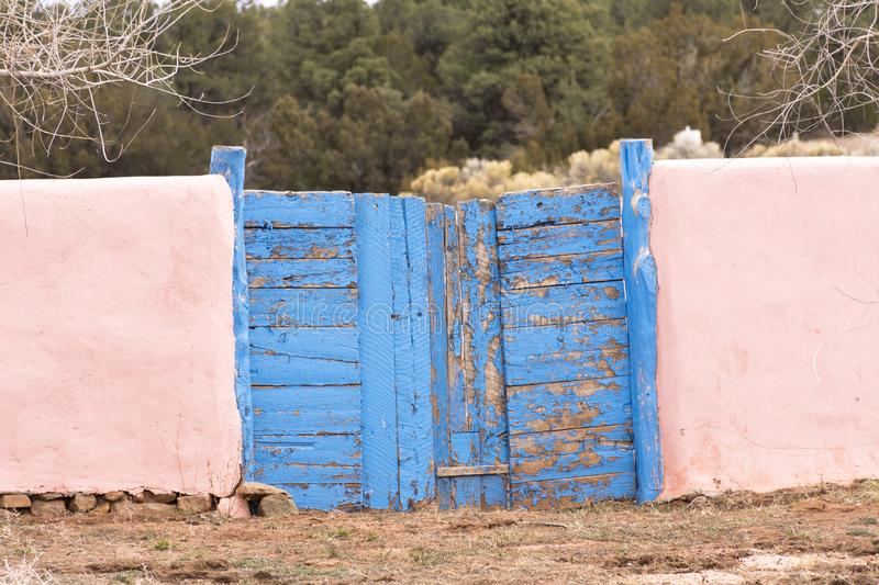 Weathered blue gates with pink adobe walls. New Mexico weathered blue gates with pink adobe walls on cloudy day stock photo
