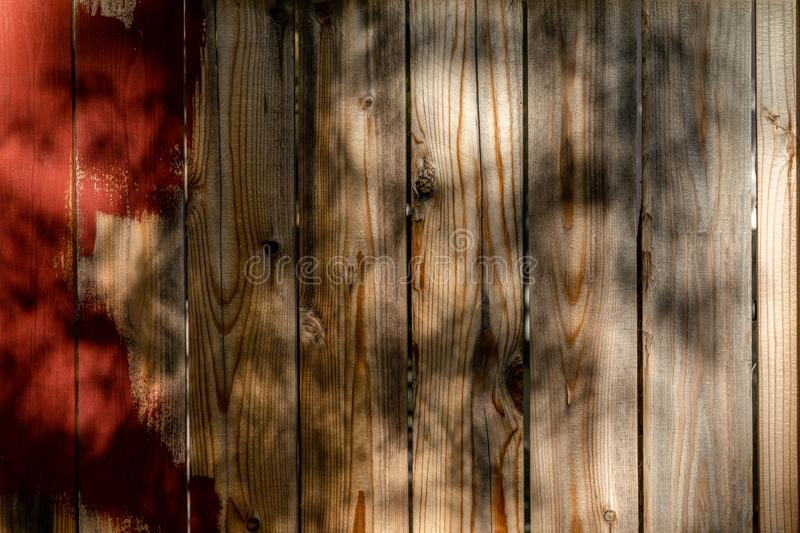 Weathered brown wood background surface with red paint. Wooden w. Brown wood background surface with red paint. Wooden wall texture planks with tree shadow royalty free stock images