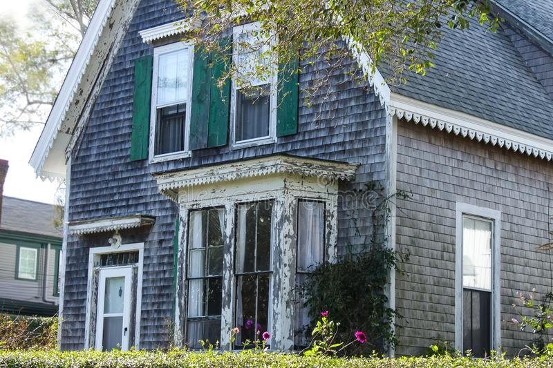 Weathered clapboard Cape Cod house with bay window and green shutters. A Weathered clapboard Cape Cod house with bay window and green shutters royalty free stock image