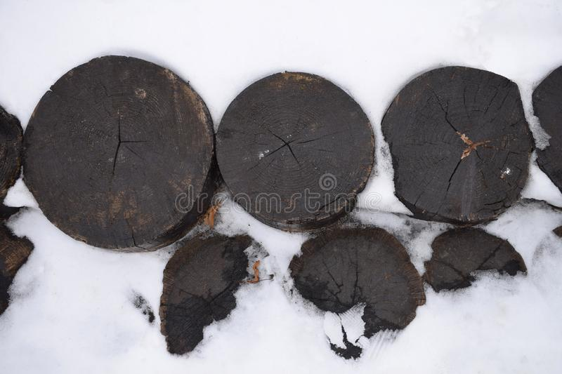 Weathered dark wooden logs in the snow stock photo