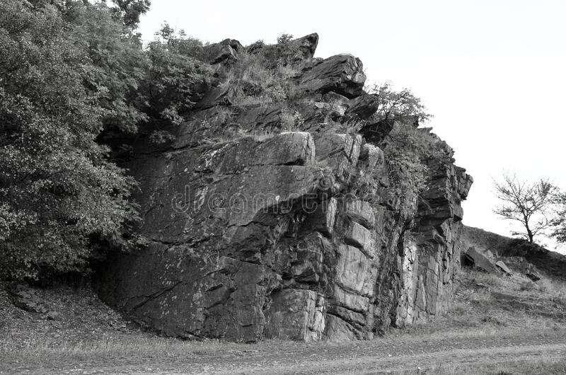 Protruding rock in a circle of vegetation. Weathered destructive rock on the background of vegetation in black and white background royalty free stock photography
