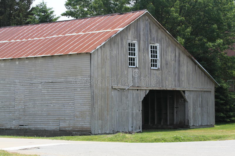 Weathered Grey Amish Barn With Red Metal Roof Stock Photo