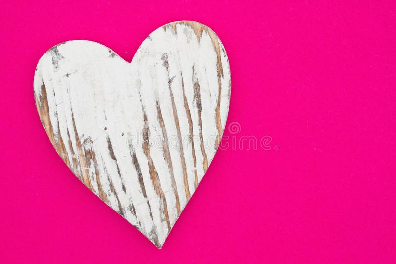 Weathered heart on bright pink textured felt material royalty free stock photos