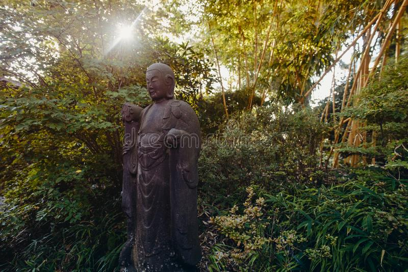 A weathered, life size stone statue of a Buddhist monk holding a walking staff and wearing prayer beads meditates under green stock photography