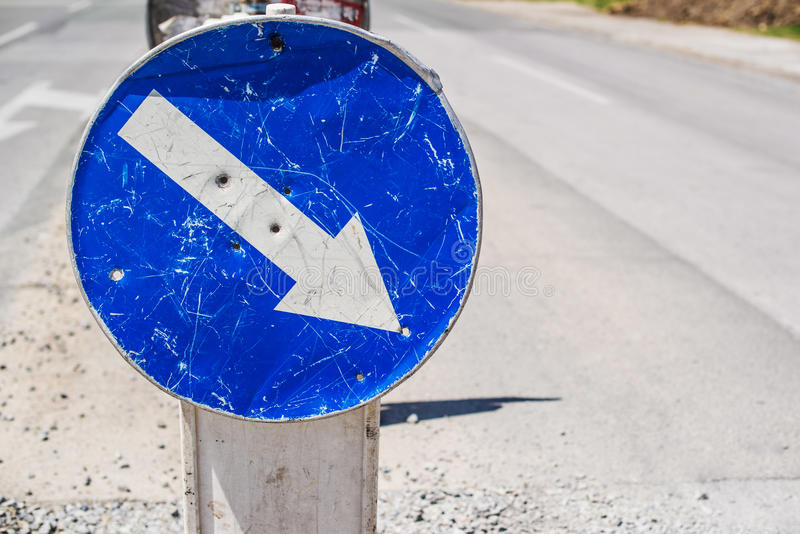 Weathered mandatory traffic direction sign. On the street stock photography