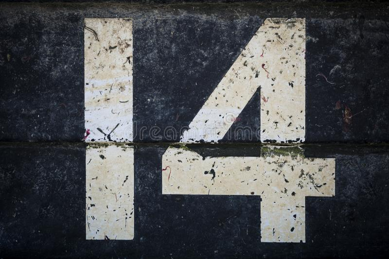 Weathered number fourteen in bold figures on black background royalty free stock images