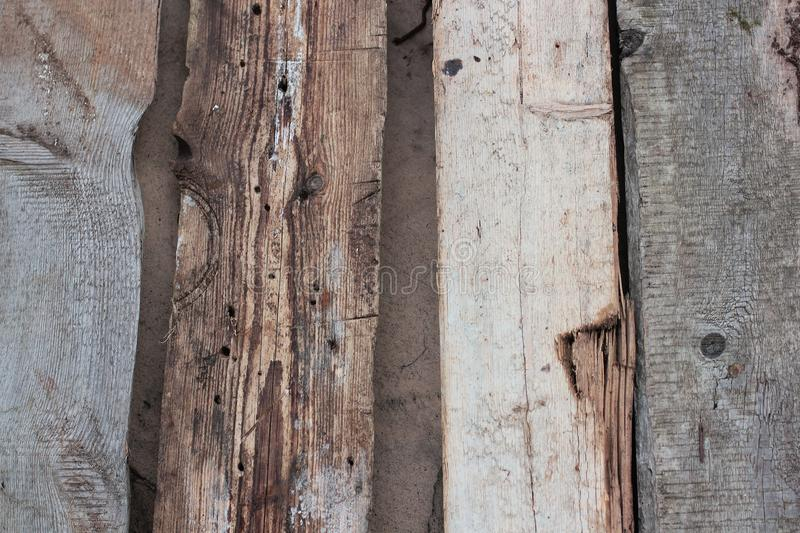 Weathered old wooden wall detail. Simple gray boards with knotholes and coarse grain nailed together. Outdoor. Backgrounds. Photo stock photos