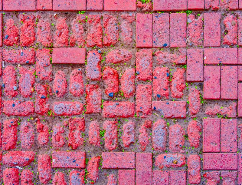 Weathered pavement made of red bricks stock images